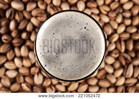 Beer and pistachios on table, top view