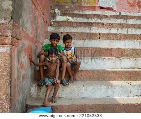 Varanasi, India - Jul 12, 2015. Children sitting on Ganges riverbank in Varanasi, India. Varanasi is the holiest of the seven sacred cities (Sapta Puri) in Buddhism, Hinduism and Jainism.