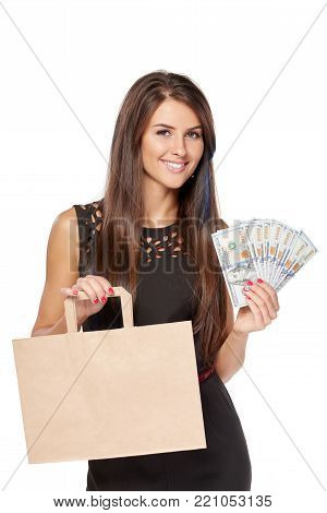 Consumerism concept. Smiling woman holding paper shopping bag with blank copy space for text and cash US dollars, over white background