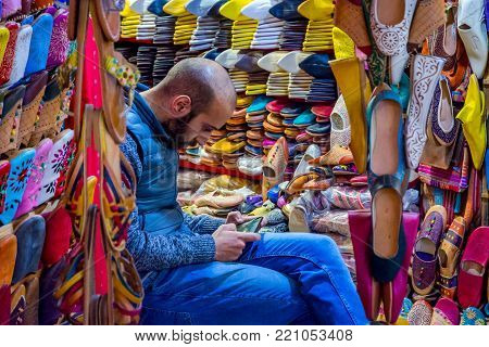 FEZ, MOROCCO - DECEMBER 10: Man playing with phone and selling colorful leather slippers in Fez old town. December 2016