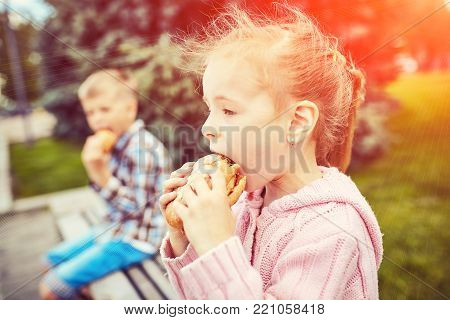 Family enthusiastically eating a hamburger outdoors  in park