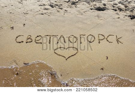 Inscription on wet sand Svetlogorsk in russian. Kaliningrad region. Russia.