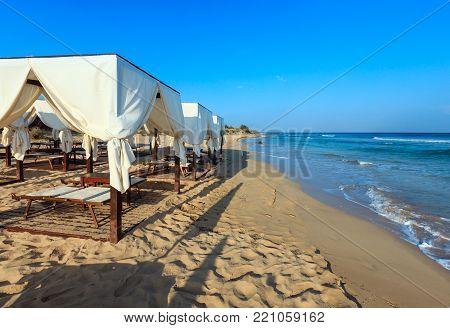 Luxury beach tents canopies on morning paradise white sandy beach Maldives of Salento (Pescoluse, Salento, Puglia, south Italy). The most beautiful sea sandy beach of Apulia.