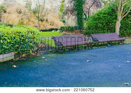 DUBLIN, IRELAND - January 6th, 2018: Saint Stephen's Green park in Dublin city centre on a calm, overcast and cold winter day with empty benches