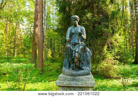 PAVLOVSK, ST PETERSBURG, RUSSIA - SEPTEMBER 21, 2017. Bronze sculpture of Euterpe -the muse of music and eloquence, with a scroll in her hand. Old Silvia park in Pavlovsk, St Petersburg, Russia