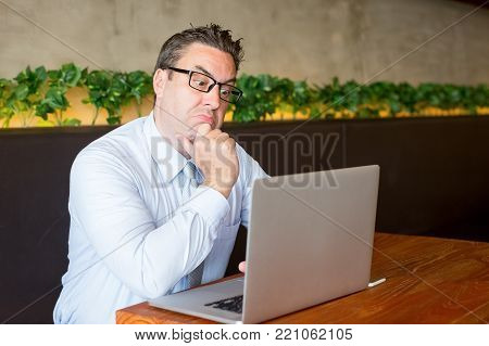 Closeup portrait of confused business man touching chin and working on laptop computer at cafe table. Business difficulty concept.