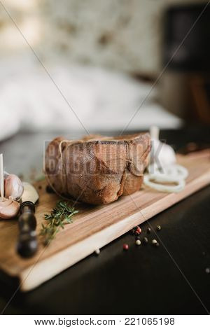 Chunk of salted smoked lard in gauze with a rope.Traditional Russian and Ukrainian meal.Healthy food with pranami spices, herbs, onion and garlic.Food photo for recipe or cookbook. Rustic clolor style poster