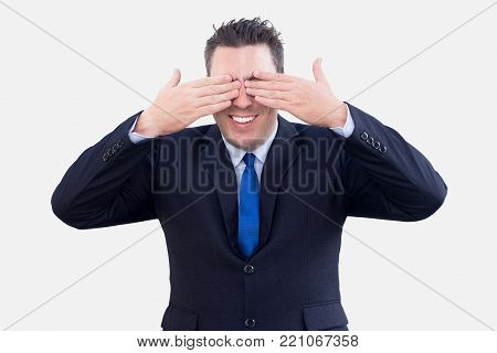 Thrilled positive businessman excited about surprise and covering eyes with hands. Smiling dreamy male employee rubbing eyes because he cannot believe his eyes. Joy concept