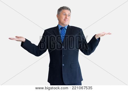 Portrait of confused mature Caucasian businessman wearing black jacket and necktie standing and shrugging shoulders. Ignorance and confusion concept