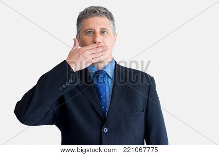 Portrait of mature Caucasian businessman wearing black jacket and necktie looking at camera and covering mouth with hand. Censorship and shock concept