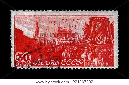 MOSCOW, USSR - CIRCA 1947: canceled stamp printed in USSR shows May Day 1st Parade on Red Square in Moscow, circa 1947. Vintage post stamp isolated on black background.