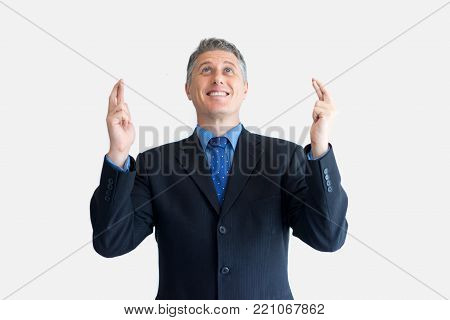 Portrait of anticipating mature Caucasian businessman wearing black jacket and necktie crossing finger and looking up. Wishing and hope concept