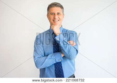 Portrait of broadly smiling CEO with hand on chin looking at camera. Middle aged business owner thinking over good deal. Business success concept