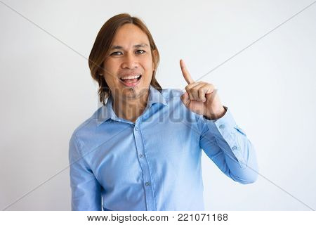 Portrait of smiling Asian guy pointing finger up. Young entrepreneur happy with his discovering. Business and new idea concept