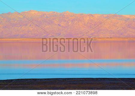 Sun setting on the Salton Sea, CA with barren mountains beyond