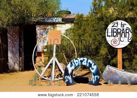 January 2, 2018 in Slab City, CA:  The front yard of a library which has hippie decorations taken in Slab City, CA which is a bohemian transient community and where people van visit this artistic and liberal community while settling down in camp sites