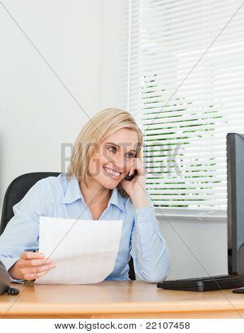 Empresaria sonriente en pantalla mientras llamando un papel en su oficina