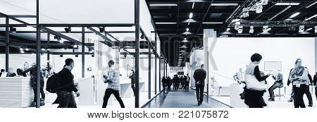 anonymous blurred business people walking between Trade show Booths, including Copy Space. ideal for websites and magazines layouts