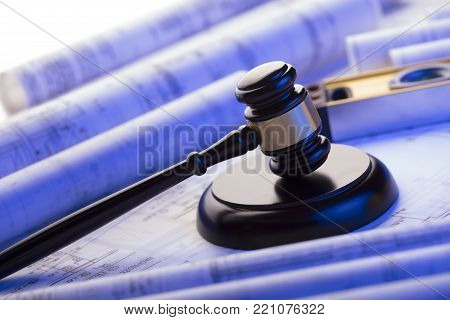 Labor and construction law. Gavel, helmet and blueprints.