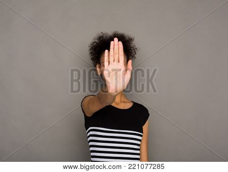 Young african-american woman covering her face with palm saying no. Girl denying proposal, making stop gesture with her hand. Studio shot, copy space