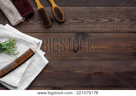 Product's for daily hair care. Comb, shampoo, towel on dark wooden background top view.