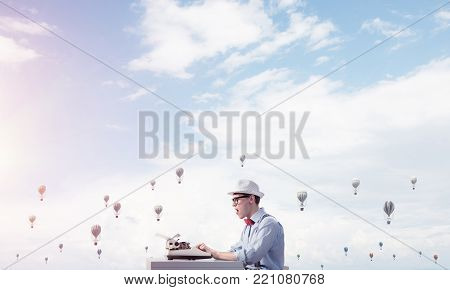 Young man writer in hat and eyeglasses using typing machine while sitting at the table with flying aerostats cloudy skyscape on background.