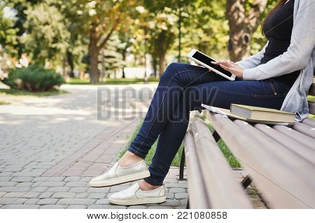 Unrecognizable woman using digital tablet. Girl working outdoors on portable computer, copy space. Technology, communication, freelance and remote working concept.