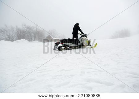 Snowmobile rider goes uphill in foggy weather.