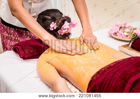 Woman is getting back skin scrub with orange salt in Thai spa