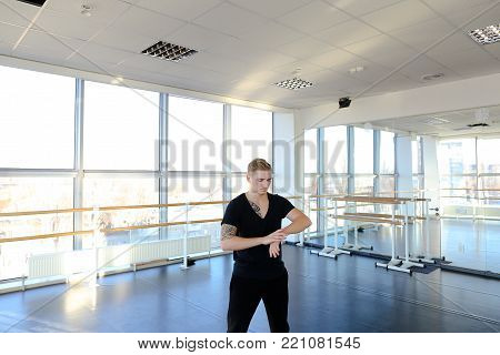 Ballet dancer do stretching exercises to keep fit, boy with good body sitting on parquet floor sloping. Fair-haired tattooed guy wearing black V-neck and trousers. Concept of sport clothes, dancing school or hall for trainings.
