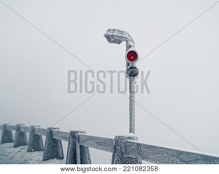 The traffic light is completely covered with snow and ice is in a snow storm along the stone fence. Red light is on. An image showing a cold winter weather.