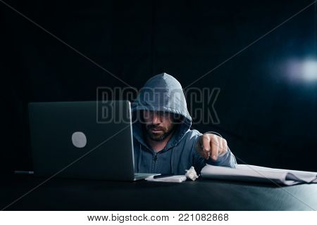 criminal mysterious male hacker hides his face, doing something illegal on a laptop
