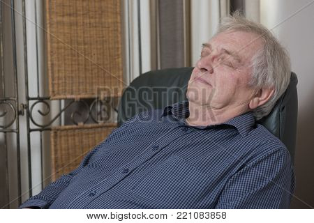 Happy mature man relaxing at home, taking a nap