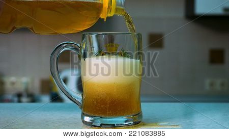 Beer Pouring From Bottle Into Glass. Close Up Of Bottle Of Beer Pouring Into A Glass. Cold Refreshme