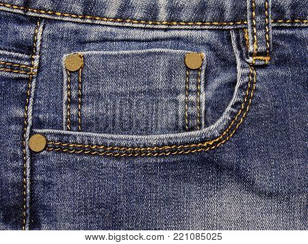 Fashion clothing from denim. Color blue with white. Yellow rivets. Stitched with a yellow thread with a large step. Double seam. The part of the double pocket is visible, the lateral and upper part of the pants.