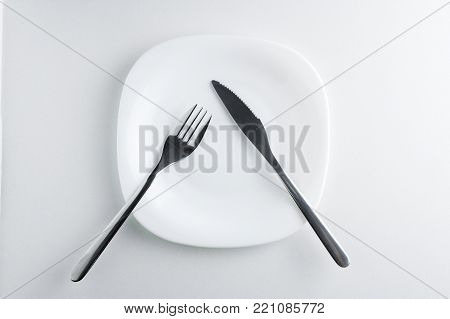 fork and knife on an empty white plate on a white background top view. Table Etiquette