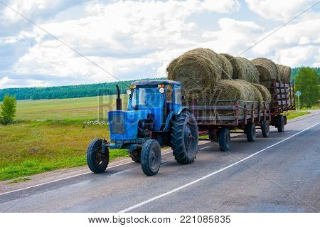 The tractor carries bales of hay on trailers
