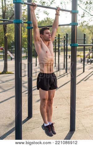 Young muscular athlete doing pull-up exercises hanging with straight arms on a horizontal bar in the park