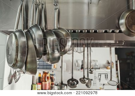 Modern shiny kitchen with stainless steell kitchenware and equipment for restaurant cooking. Closeup of frying pans