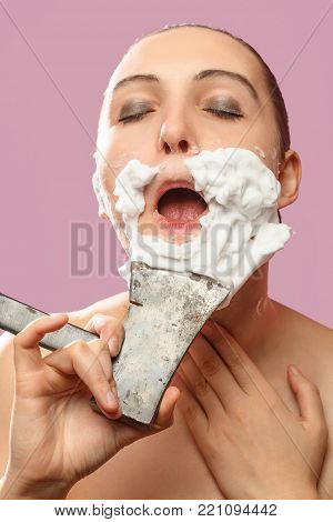 beautiful woman with fake mustache, beard on pink background has shave with axe