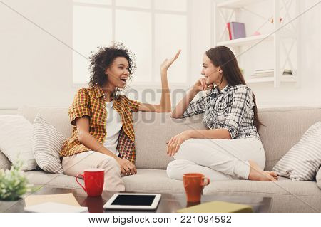 Two happy young female friends with coffee cups conversing in living room at home, chatting about their life and relations, gossip and slumber party concept, copy space