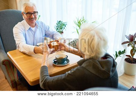 Romantic marriage proposal: loving senior man sitting at table of cozy small cafe and presenting gift box with ring to his pretty soulmate