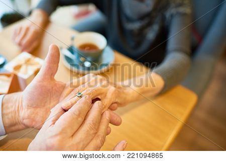 Close-up shot of unrecognizable senior man making marriage proposal to his soulmate at restaurant