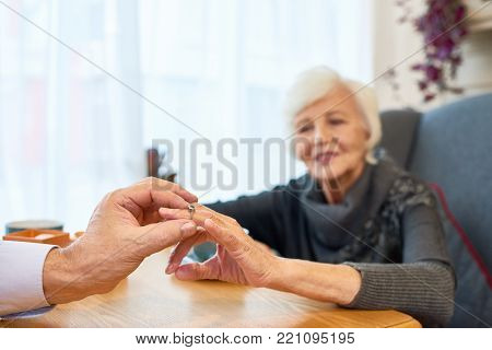 Unrecognizable senior man putting engagement ring on finger of his pretty soulmate while making marriage proposal at restaurant