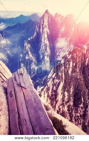 Plank Walk in the Sky at Mount Hua at sunset, worlds most dangerous hike, color toned picture, China.