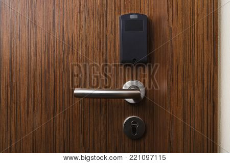 Hotel electronic card lock on wooden door. Security, room service, privacy concept