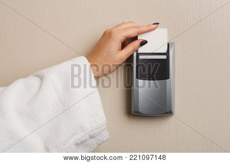 Hand inserting key card in electronic lock. Woman in white bathrobe opening hotel room door. Privacy, security, personal identification concept, copy space