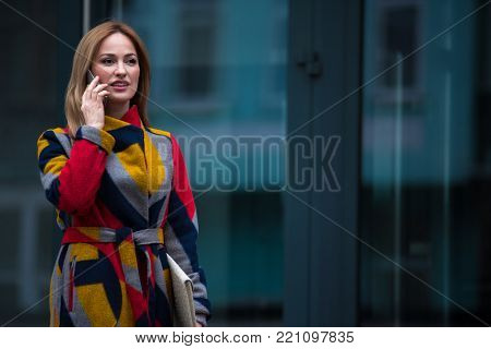 Portrait of cheerful female telling by mobile while standing near downtown. Communication concept. Copy space