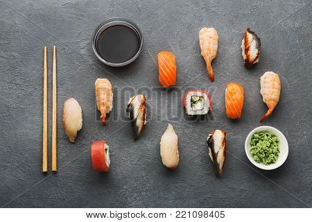 Sushi, rolls, soy sauce and wasabi on gray background. Colorful japanese restaurant food set with chopsticks for one person. Asian meals take away and delivery