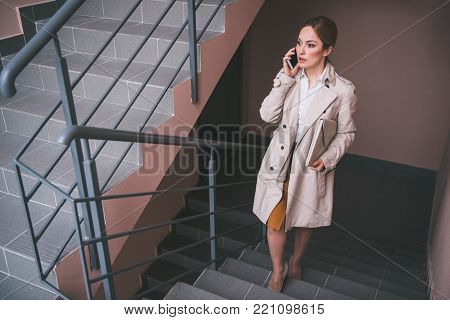 Full length portrait of serene businesswoman telling by mobile while locating in apartment. Conversation concept